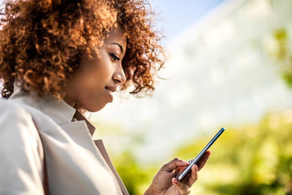 An African American woman uses a smartphone in an outdoor setting