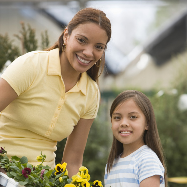 A Hispanic mother and her daughter do yard work together