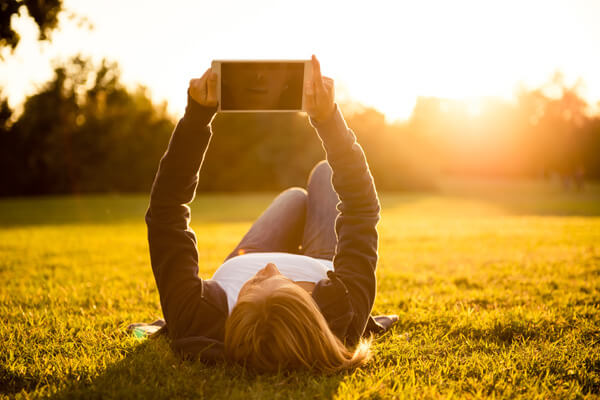 A young woman lays down the lawn and looks at her tablet